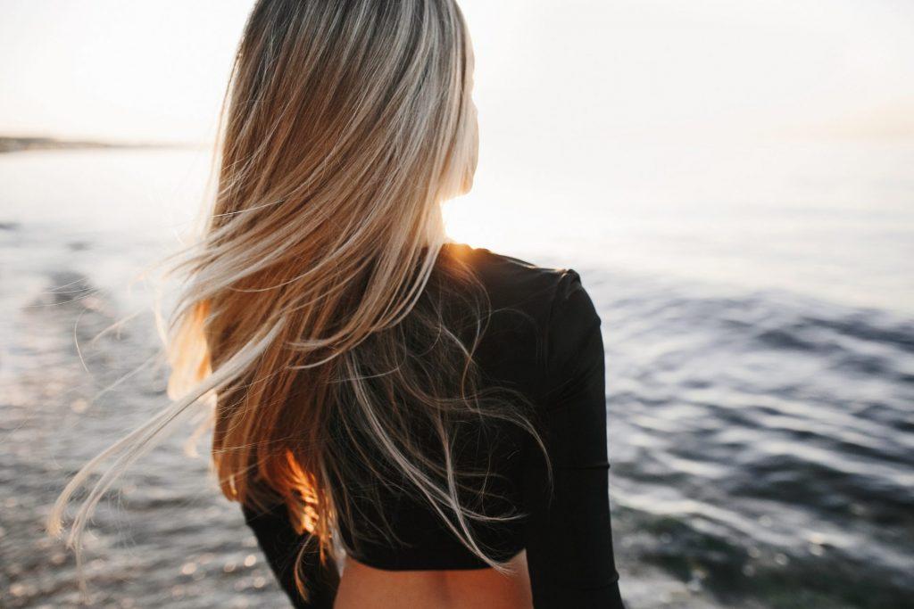 donna bionda davanti al mare di spalle