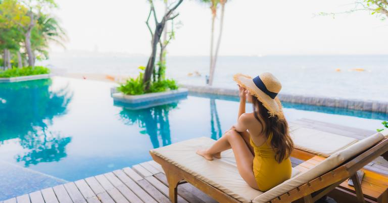 donna a bordo piscina con cappello