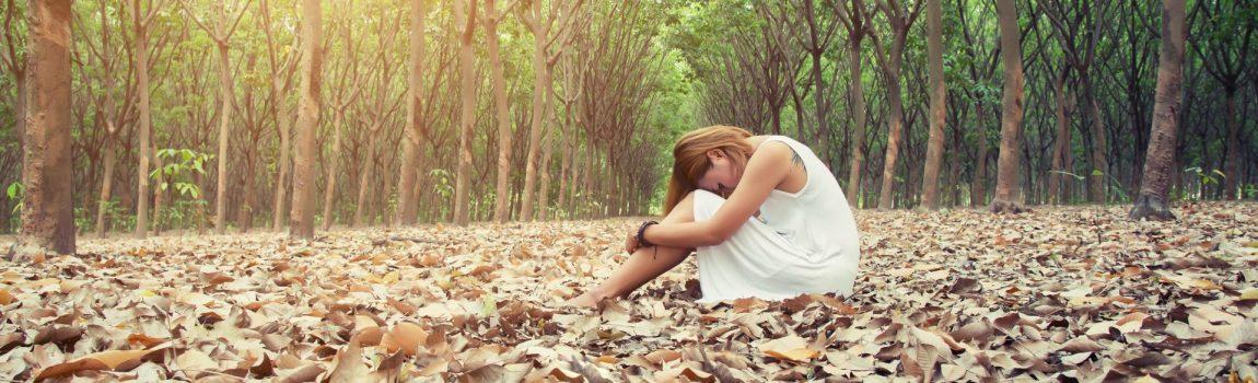 donna seduta in un bosco autunnale