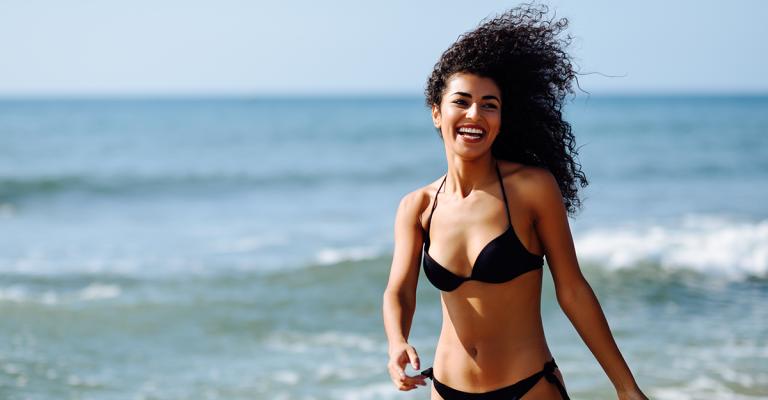 donna con capelli ricci che corre in spiaggia
